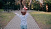 ombro : A little boy walks on a road in a park with his arms risen and tenderly hugs his mom. Slow mo, back view