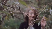 segredo : Stylish beautiful young blonde girl wades through the branches of trees, looking into the camera. slow motion