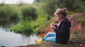 jardim de infância : A cute little girl is sitting on a river bank, eating watermelon. Blurred nature at the background. Side view