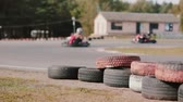 motor : Kart drivers moving on a go kart track. Coloured tires near the track. Vídeos