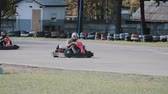 motor : Two drivers on a go-kart track move passing by a long row of coloured tires. Go-kart race.