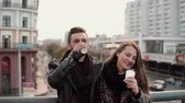 sincero : Two happy young people have fun. Handsome young man and beautiful girl laugh joyfully, holding takeaway coffee. Vídeos