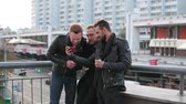 violência : Three handsome young men with beardstalk and use a smartphone. Three handsome young men near a bridge railing. Slow mo