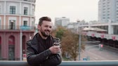 путешествие : A stylish handsome man with a beard and trendy haircut smiling cheerfully, holding takeaway coffee or tea. Slow mo