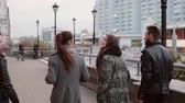 contraste : Two trendy girls and two stylish men cheerfully walk in the city and talk. Slow mo, steadicam shot, back view