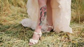 flirty : Bride shows a tattoo on her leg under a wedding dress. Surprising view of a colourful tattoo with a picture of a woman