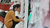 corredor : Young beautiful woman squatting in the supermarket and choosing baby clothes at showcase. Near female shopping cart. 4K