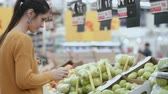 bom : Young woman choosing a green apples in the supermarket, holding one fruit and then put into the package. 4K