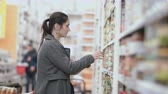 консервы : Young beautiful woman standing in front of shelves with grocery , holding one can and try choose in supermarket. 4K Стоковые видеозаписи