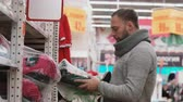 corredor : Young man choosing the goods on the shelves in the supermarket, wants to bye baby car chair, check quality. 4K