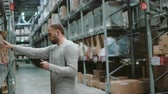 distribuidor : Young man using digital tablet in warehouse, checking goods list at supermarket. Touch the cardboard boxes. 4K Vídeos
