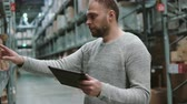 distribuidor : Young man using digital tablet in warehouse, checking goods list at supermarket and looking for items. 4K Vídeos