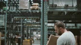 distribuidor : A man is taking boxes from the shelves, taking them and goes away through shelves in a warehouse. Back view. 4K