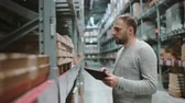 list : Young man using digital tablet in warehouse, checking goods list to buy right at supermarket and looking for items. 4K Wideo