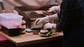 fast food : A chef in white gloves makes burgers. Man putting but on the top of hamburgers and skewers pierces each burger Back view