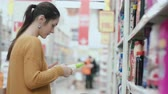 corredor : Young beautiful woman standing in front of shelves with household chemicals, holding one and try to choose. 4K Vídeos