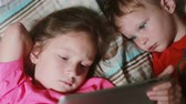 vício : Girl and boy lying on the bed and watching cartoon on touchscreen tablet. Brother and sister having rest together. Vídeos
