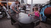 orientar : Father and daughter spending time together on a playground. Little girl and man playing air hockey. Vídeos