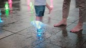 jato : Cute little boy holding mother hand and playing with water jet at the fountain in hot summer day.