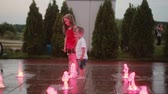 jato : Brother and sister playing at the colored fountain together. Boy and girl touching water jet, having fun. Vídeos