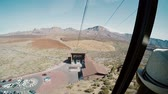 kabel : View from a ropeway cabin to mountains and station of departure. Cablecar moves up to the top of volcano.