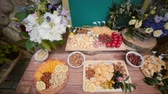 noz : Cheese table with other snacks outside. Flowers, slices cheese, nuts, eggs, drinks and tomatoes. Top view.