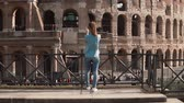Řím : Brunette tourist woman stands back to camera in Rome, Italy taking photos of the Colosseum with smartphone. Slow motion. Dostupné videozáznamy