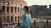 ruína : Tourist brunette woman takes photos of arch of Constantine and the Colosseum withsmartphone in Rome, Italy. Slow motion.