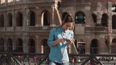 ruína : Tourist woman looks at the photos of buildings in her smartphone. Background of Colosseum in Rome, Italy. Slow motion. Vídeos