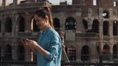 Řím : A young tourist woman takes selfie photo at the Colosseum in Rome, Italy with smartphone smiling, laughing. Slow motion.