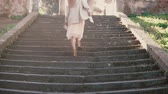 получать : Young stylish woman walking in the city old street, climbing the stairs. Girl spending vacation in Europe.