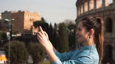 mosolyogva : Young happy woman takes selfie on her smartphone in Rome, Italy, enjoying the trip, watching the pictures. Slow motion. Stock mozgókép