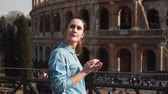utilização : Young woman uses her smartphone in Rome, Italy against the background of Colosseum, looking a little sad. Slow motion. Stock Footage
