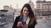 vacation : Brunette woman walking in city centre and using smartphone. Girl texting with someone, spending vacation in Rome, Italy. Stock Footage