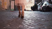 вид : Woman walking on cobblestone pavement road. Girl exploring new city wearing in shoes and skirt. Close-up view.