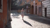 estilos de vida : Street portrait of young beautiful fashionable woman walking at the old city. Girl looking around, exploring the town. Stock Footage