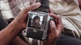 contraste : Close-up view of african man holding old photocamera, taking photo portrait beautiful woman. Multiracial couple on bed. Stock Footage