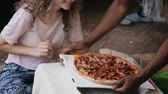 cheiro : African man in pajamas brings pizza to hungry caucasian woman. Multiracial couple in pajamas smell the fast food.