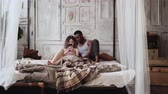 utilização : Multiracial couple in pajamas on the bed uses the smartphone. African man and european woman browse the Internet. Stock Footage