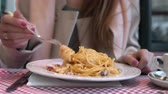 conforto : Young happy woman sitting at the table in cafe and enjoying the meal. Hungry woman eating tasty pasta.
