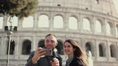 Řím : Young happy couple traveling in Rome, Italy. Man and woman taking the selfie photo on smartphone near the Colosseum.