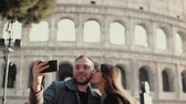 coliseum : Young attractive woman and man standing near the Colosseum in Rome, Italy. Couple takes the selfie photo on smartphone.