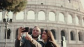 Řím : Happy young couple using smartphone for taking selfie photo near Colosseum in Rome, Italy. Man and woman have vacation.