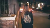 cień : Brunette woman with backpack walking late at night. Attractive girl goes through the city centre near road in evening.