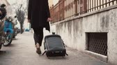 chegar : Traveler woman legs walking carrying a suitcase in a city street. Girl come on vacation in Europe. Vídeos
