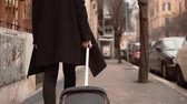 chegar : Female arrive in new city for business trip. Businesswoman with suitcase walking on the sidewalk, exploring the city.