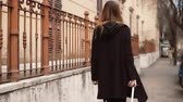chegar : Young woman walking in the city centre. Girl with baggage moving to new place and now exploring the city. Slow motion.