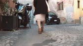 évjárat : Close-up view of young stylish woman walking on cobblestone pavement road. Girl going through the street. Slow motion.