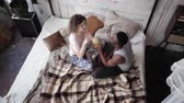 unidade : Multiethnic couple sit on the bed and twist the globe. Man and woman pick the destination to travel, hug and kiss.