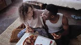 alimentação pouco saudável : Happy multiethnic couple sitting on the flow, hugging and eating fast food. Woman feed the hungry man a slice of pizza. Stock Footage